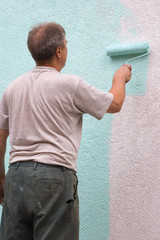 man painting wall with a roll in green