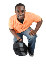 Student kneeling with a bag looking up smiling