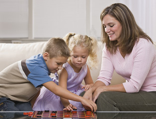 Woman Playing Checkers With Children