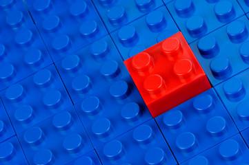 Roter Bauklotz in einem Feld blauer