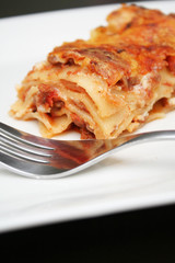 Serving of lasagna on white plate with a fork