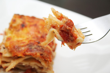 A bite of lasagna on a fork