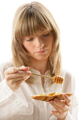 Portrait of young woman applying honey on bread