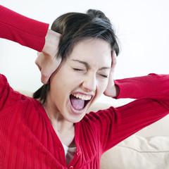 femme criant en se bouchant les oreilles
