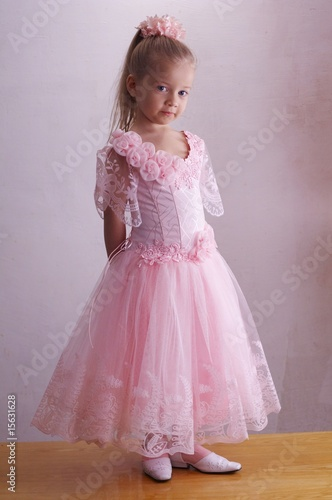 The smiling girl in a pink dress standing on a table
