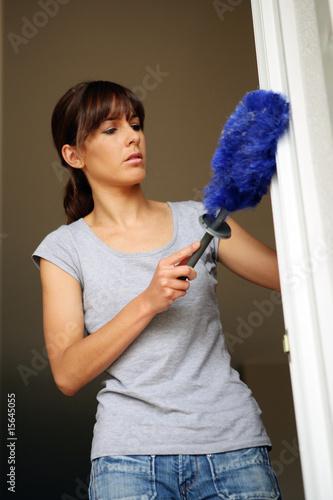 Femme faisant la poussi re avec un plumeau dans une maison - Poussiere dans la maison ...