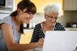 Sénior devant un ordinateur portable près d'une femme souriante