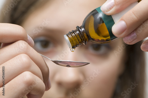 Dripping herbal essence of a vial over a spoon