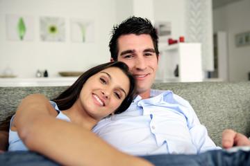 homme et d'une femme souriants assis sur un canapé
