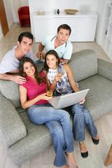 Groupe d'amis devant un ordinateur portable avec un verre de vin