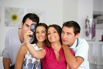 hommes et femmes se photographiant avec un téléphone portable
