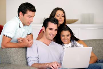 hommes et de femmes devant un ordinateur portable