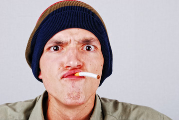 Funny face young man with cigarete in hand
