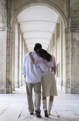 Young couple walking in an old European colonnade
