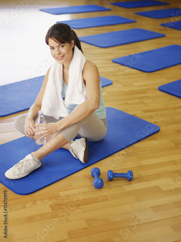 Woman on exercise mat with water bottle and hand weights