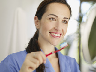 Woman brushing teeth smiling