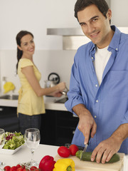 Man in kitchen chopping vegetables with woman