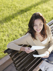 Woman sitting on wooden bench with personal letter smiling