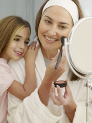 Woman in robe applying makeup in mirror with girl smiling