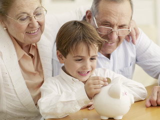 Grandparents teaching grandson to save money in a piggy bank