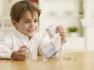 Boy counting money in glass jar