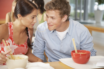 Teenage boy and girl sharing noodle in cafeteria