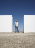 Man standing between two walls outdoors