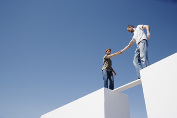 Two men atop two walls balancing on a plank