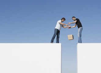 Two men atop two walls dropping a box