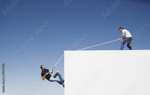A man helping another man climb up a wall