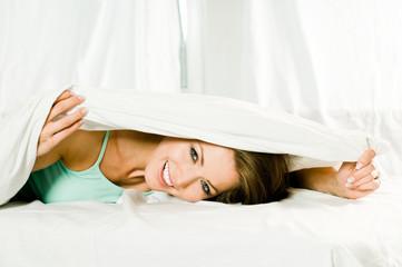 Frau unter der Bettdecke lacht