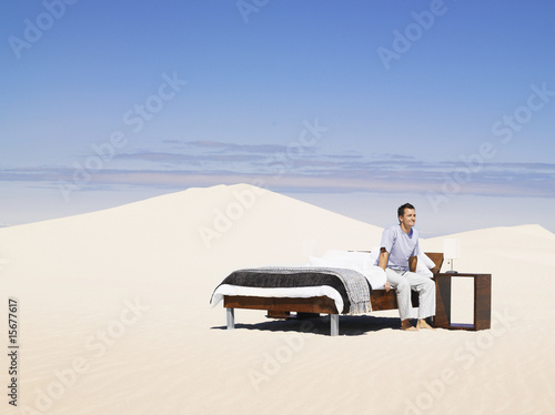 A man sitting in a bed outdoors