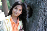 Young girl relaxing against tree. Part Thai - Scandinavian poster