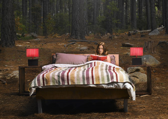 A woman reading in a bed outdoors in the woods