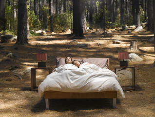 A couple sleeping in a bed outdoors in the woods