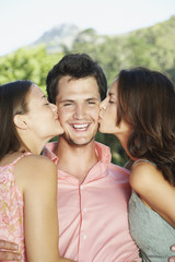 A young man with two young woman embracing him