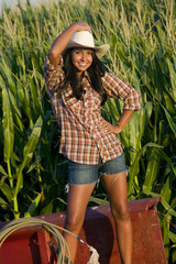A woman standing on a pickup truck in a corn field