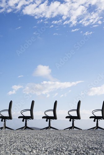 Line-up of empty office chairs in the middle of nowhere