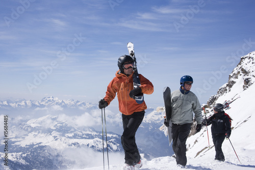 Skiers and snowboarder walking up mountain
