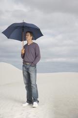 A man with an umbrella outdoors