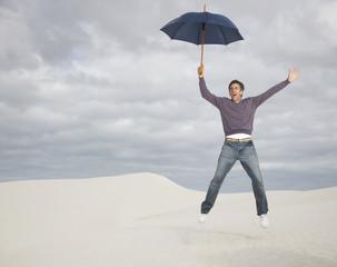 A man jumping with an umbrella outdoors