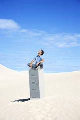 Man sitting on filing cabinet looking to the sky