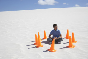 A man surrounded by traffic cones in the middle of nowhere