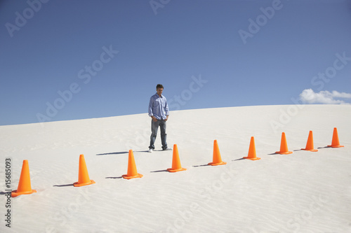 A man with traffic cones in the middle of nowhere