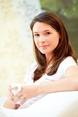 Schöne Frau zuhause mit Kaffeetasse