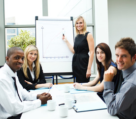 Attractive businesswoman giving a presentation smiling at the ca