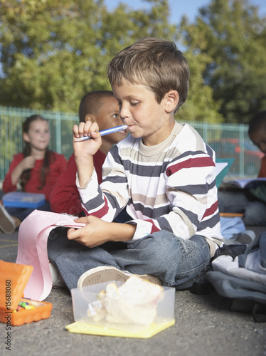 Students outside of school eating and writing