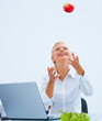 Pretty business woman playing with a apple by laptop at desk