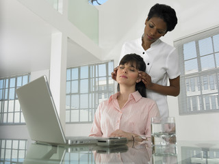 A businesswoman on a laptop getting a temple massage