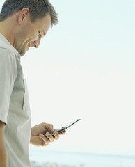 A man looking at his cellular phone